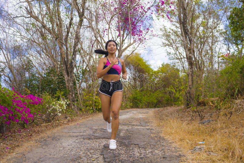 Ung attraktiv och exotisk asiatisk indonesisk löparekvinna i jogga genomkörare utomhus på spring för natur för bygdvägspår arkivbild