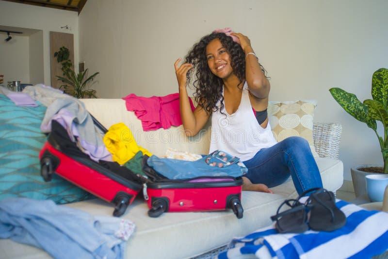 Ung attraktiv och galen lycklig latin - den amerikanska kvinnan som förbereder kläder som packar material i resväskan som lämnar  royaltyfri foto