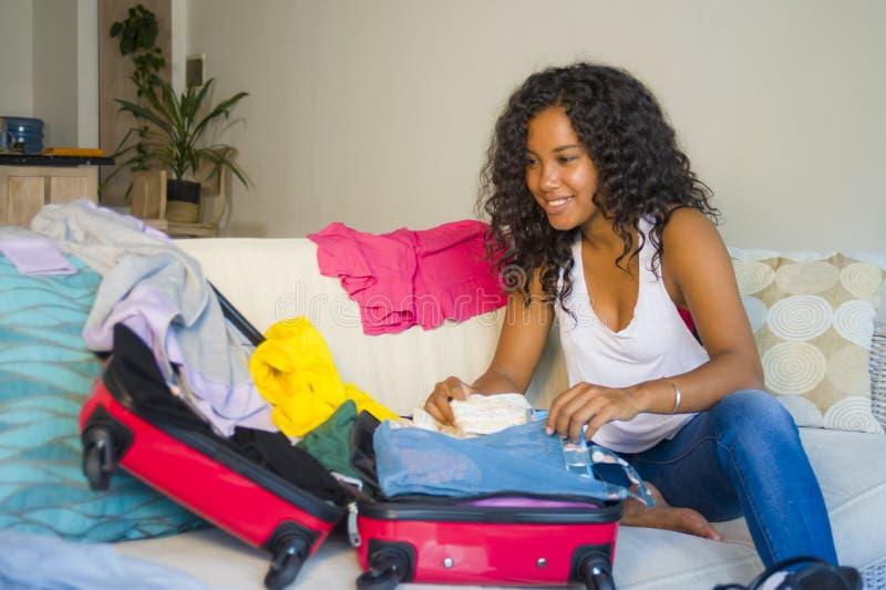 Ung attraktiv och galen lycklig latin - den amerikanska kvinnan som förbereder kläder som packar material i resväskan som lämnar  arkivfoto