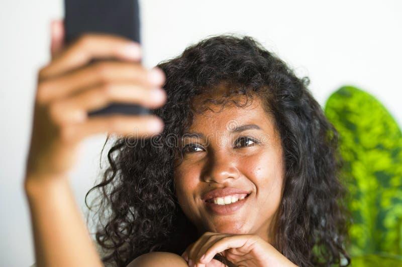 Ung attraktiv och härlig lycklig svart afro amerikansk kvinna som tar selfieståendebilden med mobiltelefonen på ferieapartm fotografering för bildbyråer