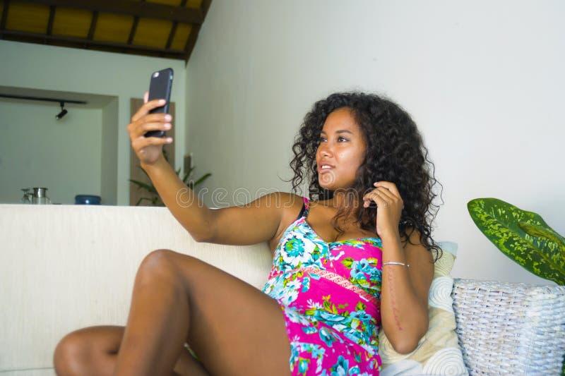 Ung attraktiv och härlig lycklig svart latin - amerikansk kvinna som ifrån varandra tar selfieståendebilden med mobiltelefonen på fotografering för bildbyråer