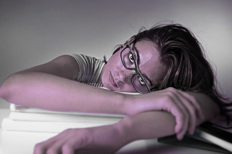 Ung attraktiv och härlig trött studentflickabenägenhet på tröttat och evakuerat studera för skolbokhög arkivbild