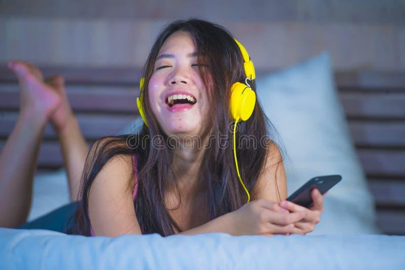 Ung attraktiv och lycklig asiatisk kinesisk kvinna med gul hörlurar som lyssnar till musik i mobiltelefon på hemmastadda le mumme royaltyfria bilder