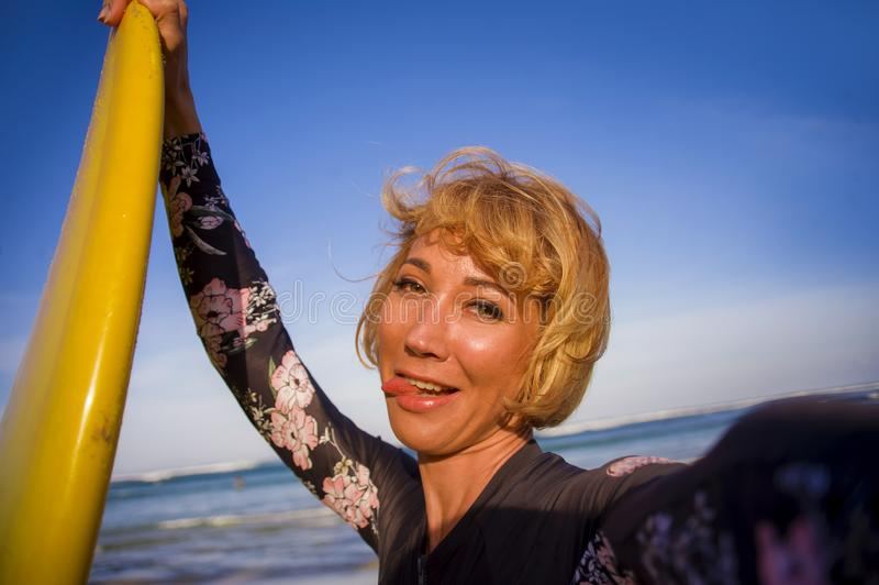 Ung attraktiv och lycklig blond surfarekvinna i hållande bränningbräde för baddräkt i stranden som tar smi för självståendeselfie royaltyfri bild