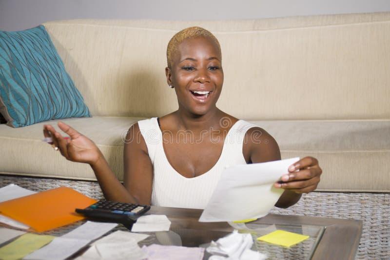 Ung attraktiv och lycklig lyckad svart afro amerikansk kvinna som in ler tillfredsställda inhemska redovisningsaffärsskatt och be royaltyfri fotografi