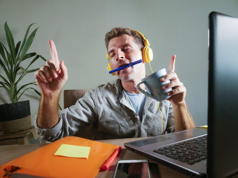 Ung attraktiv och lycklig man med gul hörlurar som sitter det hemmastadda kontorsskrivbordet som arbetar med bärbar datordatoren  royaltyfri foto