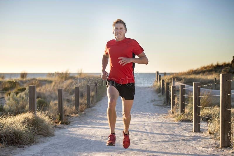 Ung attraktiv och lycklig sportlöpareman med passformen och stark sund kropputbildning på av vägspår i rinnande genomkörare för s royaltyfri bild