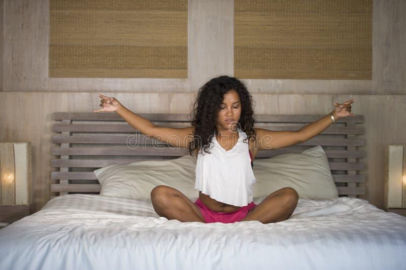Ung attraktiv och lycklig svart latin - övar det hemmastadda sovrummet för den amerikanska kvinnan som gör yogameditation, och kr arkivfoto