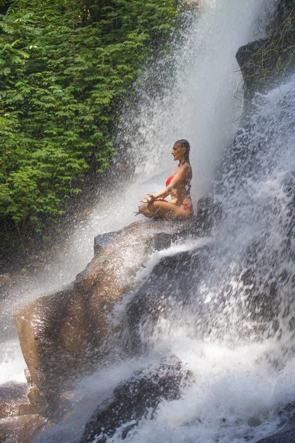 Ung attraktiv och lycklig 30-talkvinna med strömmen för vattenfall för paradis för praktiserande yoga för passformkropp den våta  arkivfoto