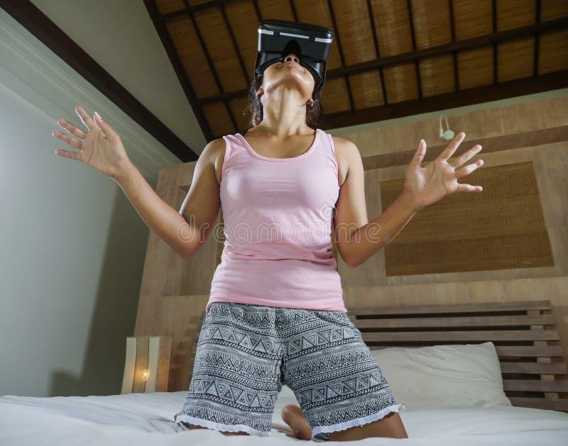 Ung attraktiv och lycklig tonårig flicka på säng som spelar med videospelet för VR-virtuell verklighetskyddsglasögon som har roli royaltyfria foton