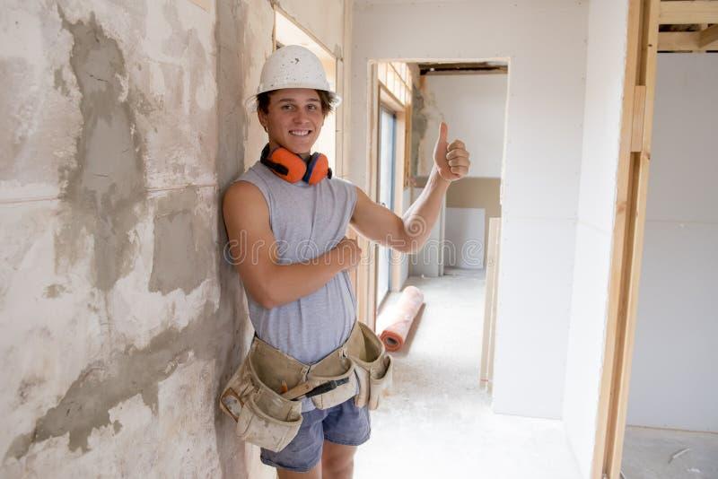 Ung attraktiv och säker byggmästare- och konstruktörjobbdeltagare i utbildning som lär och arbetar på den blåa kragen för industr arkivfoto