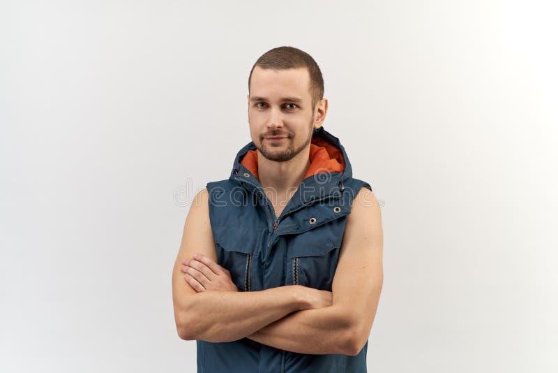 Ung attraktiv säker man som poserar för en stående med vikta armar, iklädd sportig all-säsong tunikaöverkant royaltyfri bild