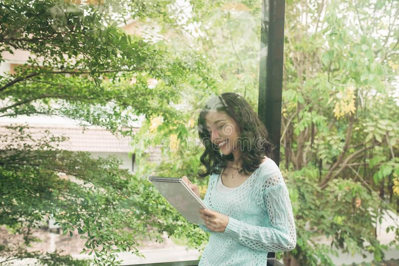 Ung attraktiv söt flicka med notepaden på en veranda 9 inställda underbara fjädertulpan för mood mångfärgade bilder arkivfoto