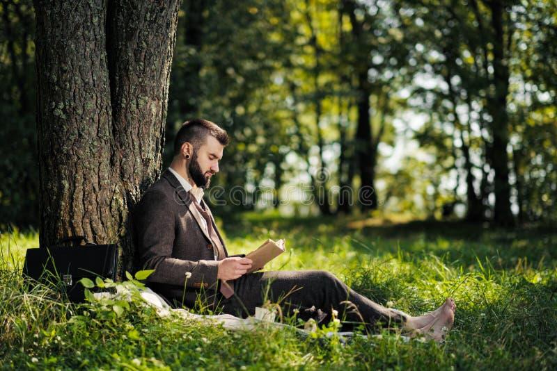 Ung attraktiv skäggsföretagare som sitter på gröngräs under träd och vilar i park Läs bok, drick kaffe arkivfoto