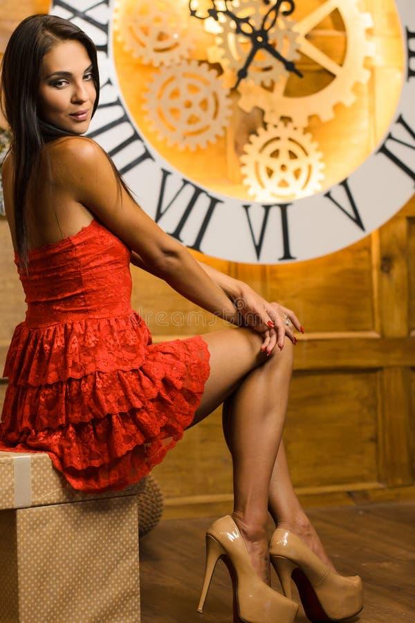 Ung attraktiv smal kvinna med rak hår i röd kvällskläck som står mot bakgrund av stor väggklocka arkivfoto