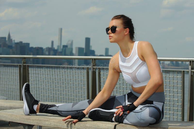 Ung attraktiv sportig kvinna som gör sträcka övningar royaltyfri bild