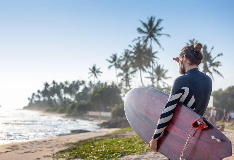 Ung attraktiv sportig stilfull man med en surfingbräda i hans händer mot bakgrundshavet royaltyfri bild