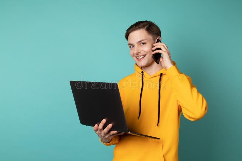 Ung attraktiv startcofunder i gul hoodie genom att använda bärbara datorn och tala på mobiltelefonen royaltyfria foton