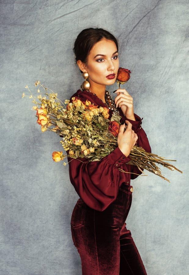 Ung attraktiv stilfull brunettkvinna med buketten av ursnygga torra rosor som bär vinous clothers och guld- smycken royaltyfri fotografi