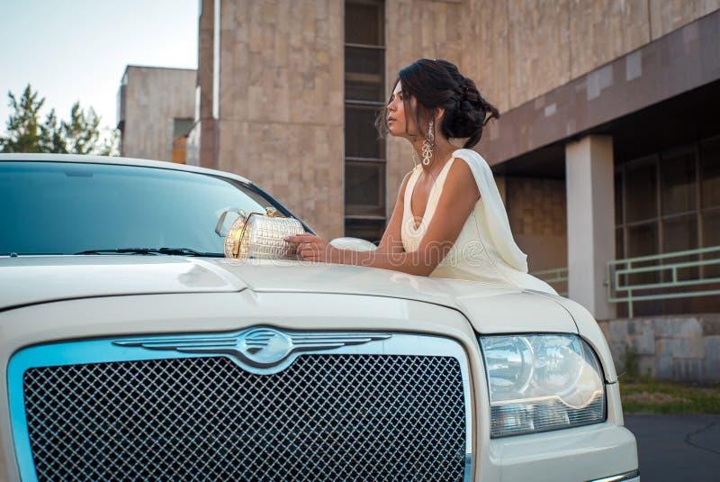 Ung attraktiv storgubbekvinna i klänningställningen nära den vita limousineet arkivfoton