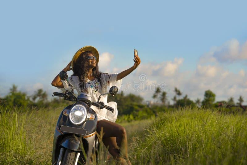 Ung attraktiv svart afro amerikansk turist- kvinna i den asiatiska traditionella hattridningmopeden som tar selfiefotoet med mobi royaltyfri foto