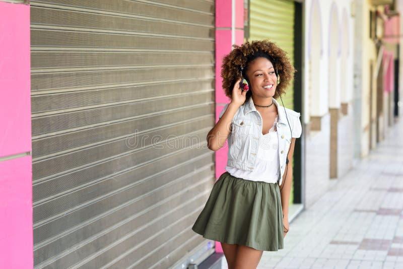 Ung attraktiv svart kvinna i stads- gata som lyssnar till musiken med hörlurar Flicka som bär tillfällig kläder med afro arkivbild