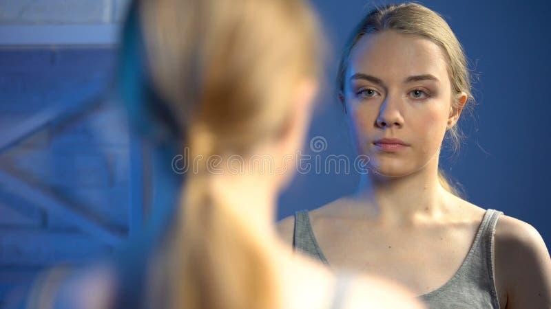 Ung attraktiv tonårs- flicka med naturlig makeup som ser i spegelreflexion royaltyfria foton