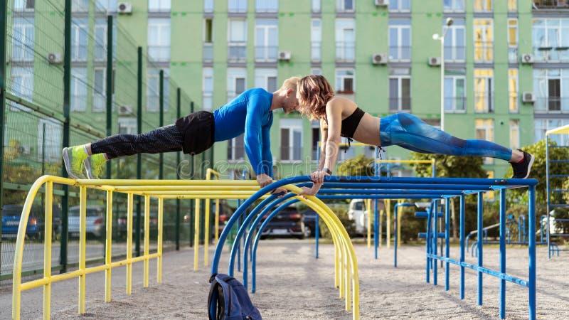 Ung attrective crossfitman och kvinna som utarbetar på sportsgrounden royaltyfria foton