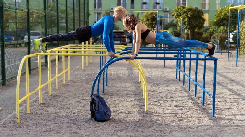 Ung attrective crossfitman och kvinna som utarbetar på sportsgrounden fotografering för bildbyråer