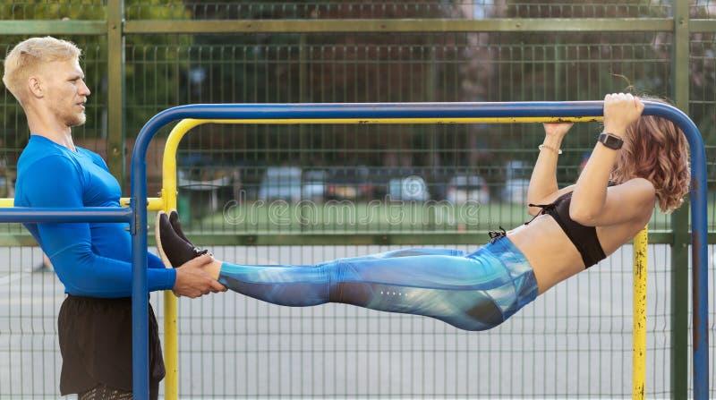 Ung attrective crossfitman och kvinna som utarbetar på sportsgrounden arkivfoto