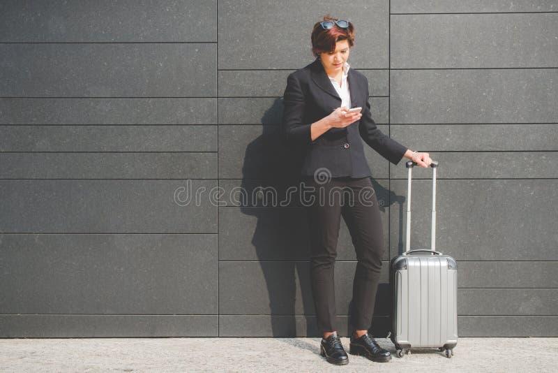 Ung autentisk affärskvinna som ser hennes smartphone i fena royaltyfri bild