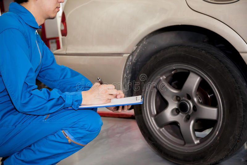 Ung automatisk tekniker som kontrollerar på bilgummihjul i garage royaltyfria foton