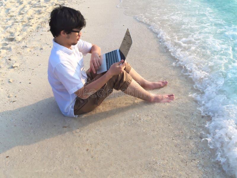 Ung avkopplad man med bärbara datorn som sitter på den sandiga stranden med mjuka vågor Internet av sakerbegreppet royaltyfri fotografi