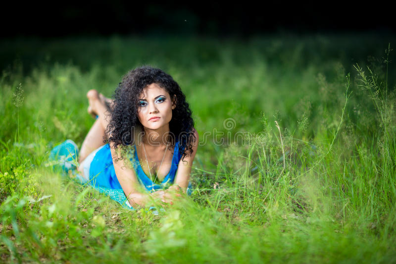 Ung avslappnande kvinnlig som ligger på hennes mage i gräset arkivfoto