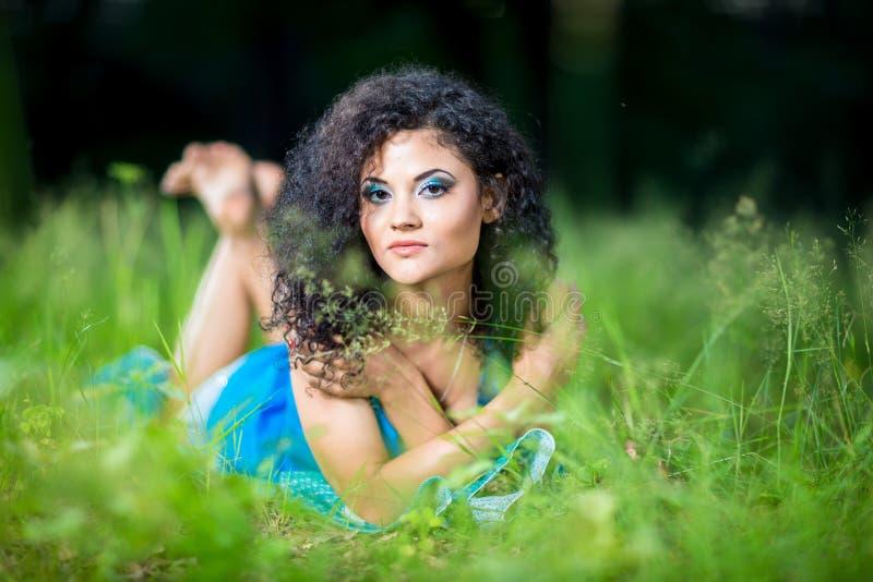 Ung avslappnande kvinnlig som ligger på hennes mage i gräset arkivfoton