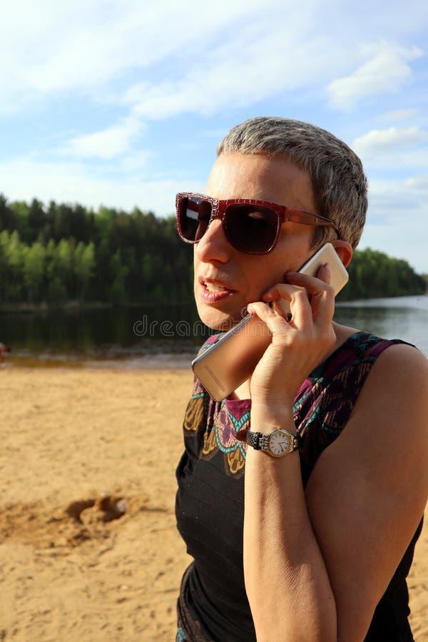 Ung bärande solglasögon för affärskvinna som talar på mobiltelefonen royaltyfria foton