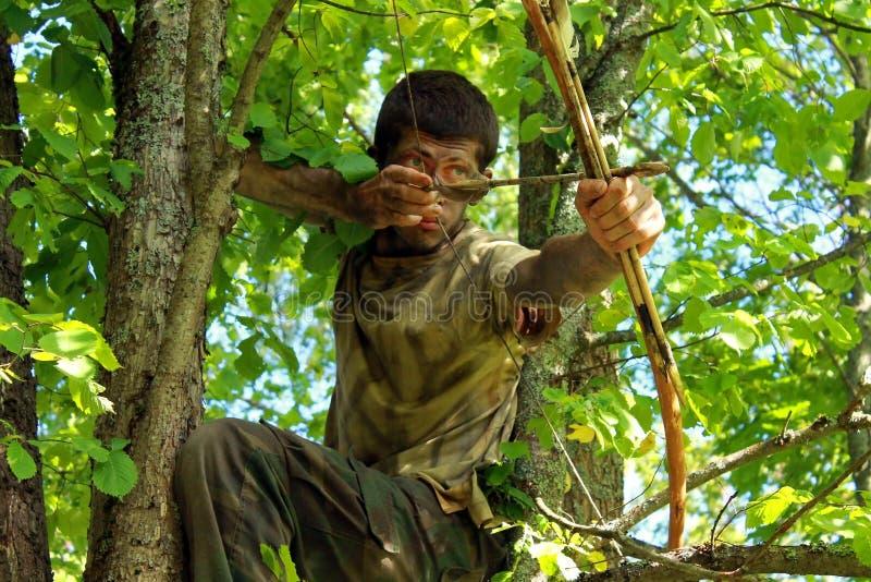 Ung bågskytt i skog royaltyfria bilder