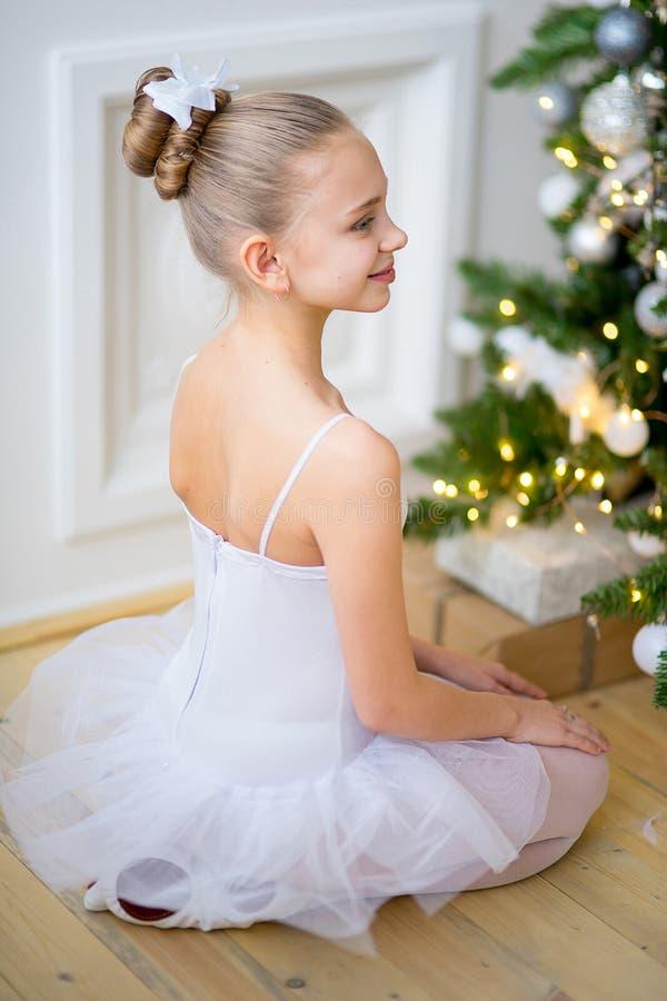 Ung balettdansör som sitter nära julgranen royaltyfri foto