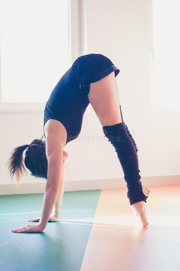 Ung balettdansörkvinna som gör sträckning arkivbild