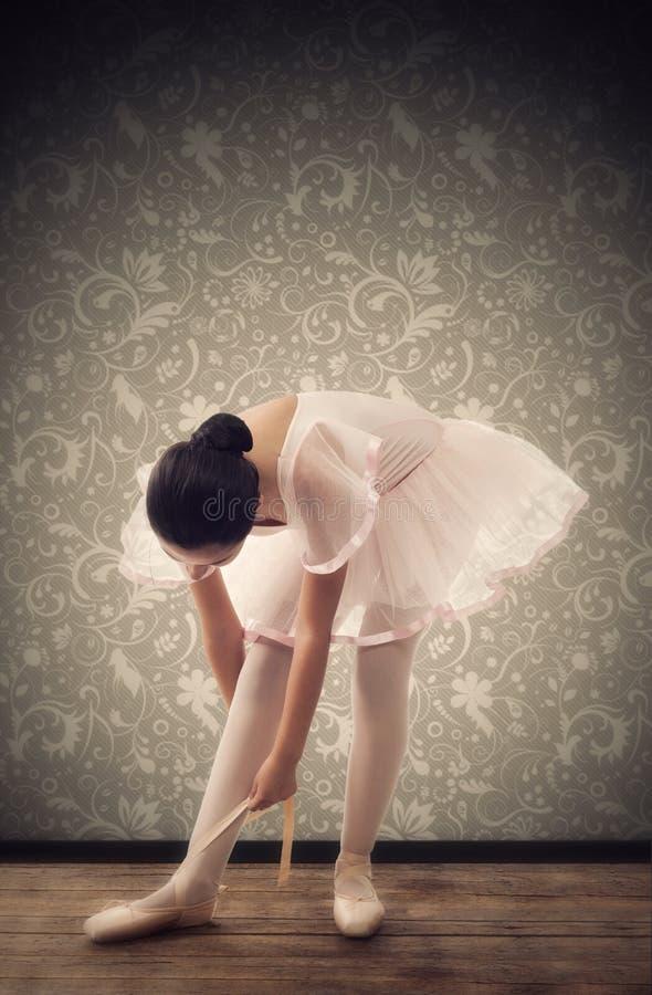 Ung ballerina, medan binda balettskor arkivfoton