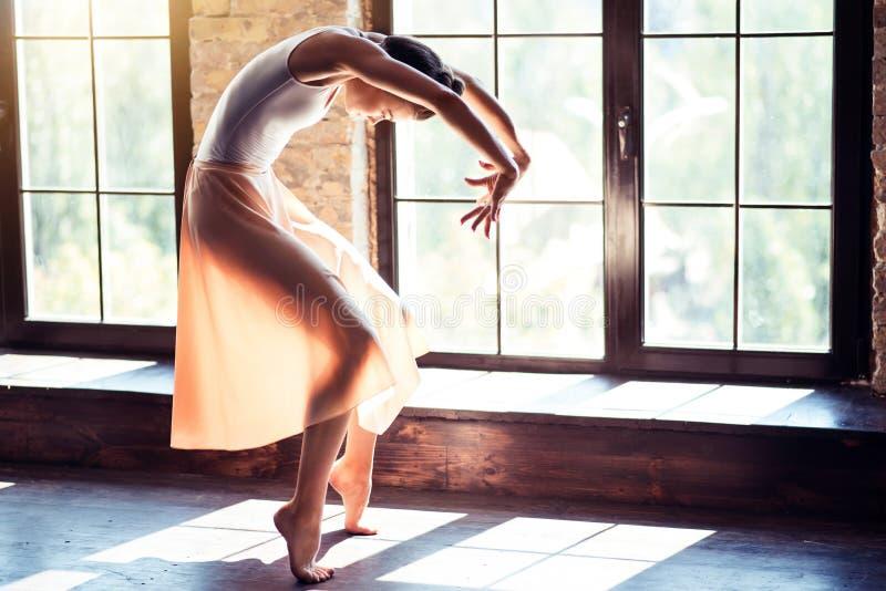 Ung ballerina som repeterar hennes dans i en idrottshall arkivfoton