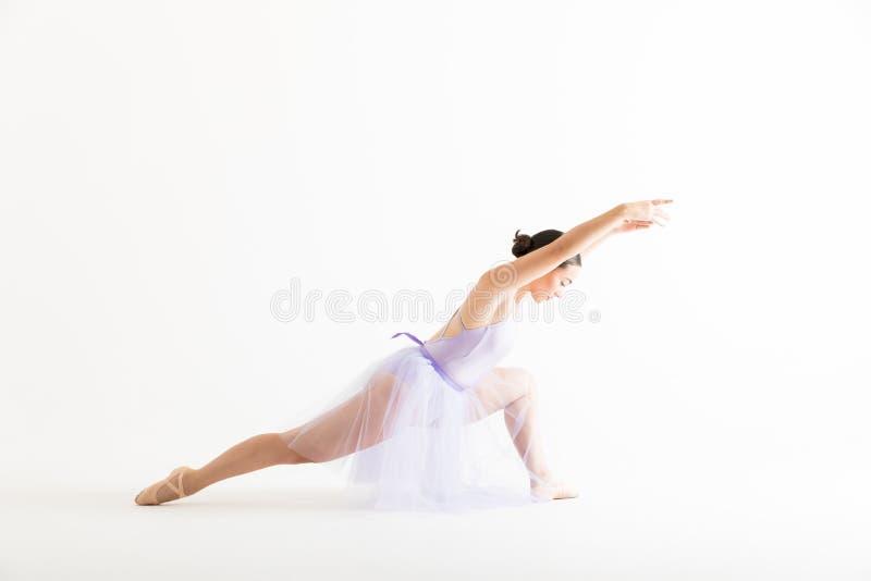 Ung ballerina som repeterar med armar som ifrån varandra lyfts, och ben arkivfoto