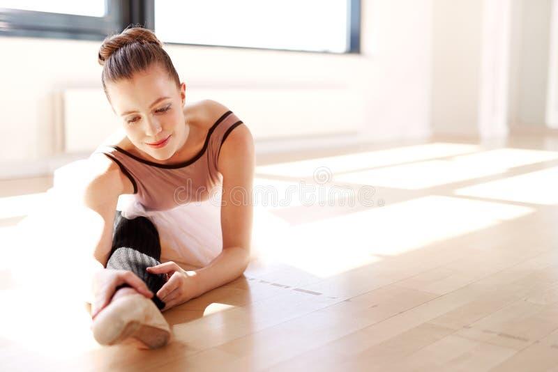Ung ballerina som sträcker benet i Sunny Studio arkivfoton