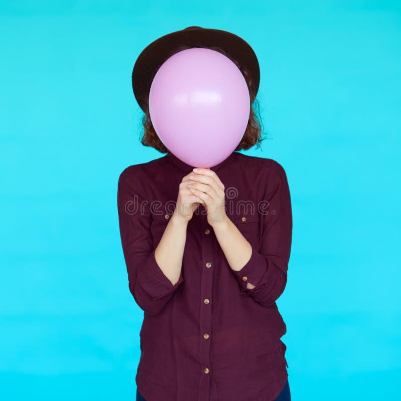 Ung ballong för hipsterkvinnainnehav över hennes framsida arkivbilder