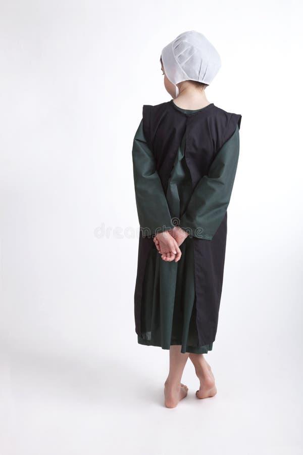 Ung barfota Amish flicka som isoleras på en bakgrund royaltyfri bild