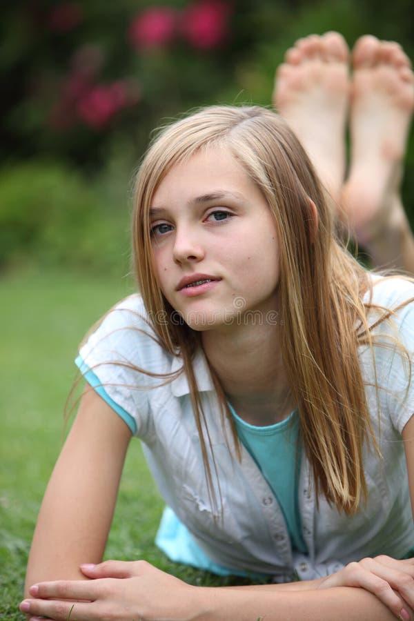 Ung barfota tonåring som kopplar av på gräset royaltyfri foto