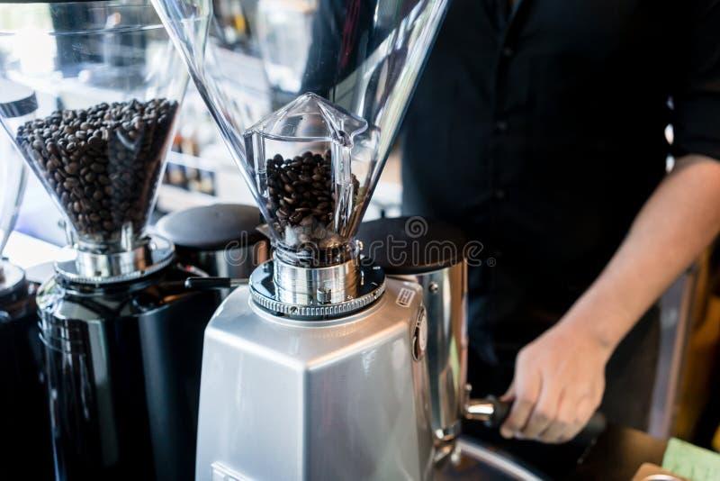 Ung barista som förbereder kaffe från nya grinded grillade bönor arkivbilder