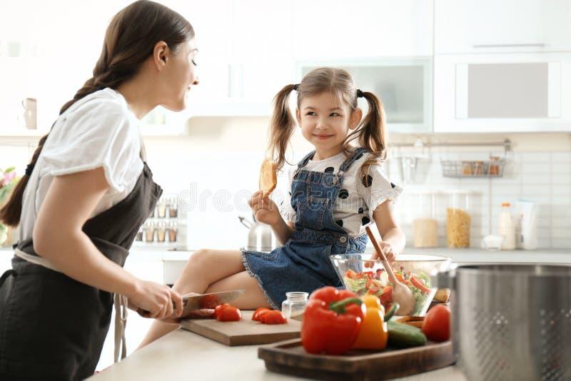 Ung barnflicka med den gulliga lilla flickan som tillsammans lagar mat royaltyfria foton