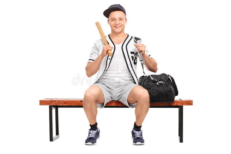 Ung basebollspelare som rymmer ett baseballslagträ arkivfoton