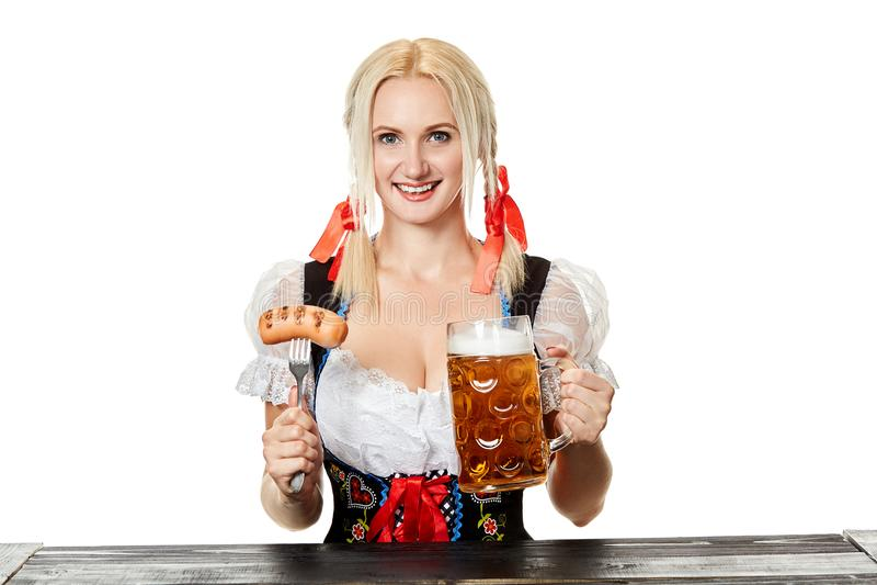 Ung bavariankvinna i dirndlsammanträde på tabellen med öl på vit bakgrund arkivbilder